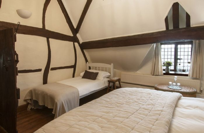 Second floor: Family bedroom with an A-frame cruck beam and exposed timbers, with a 6' super-king bed and a 3' single bed