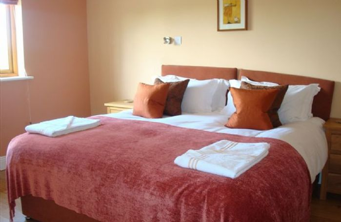 First floor: Double bedroom with en-suite bathroom with walk in shower and views over the courtyard.
