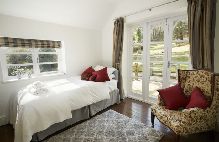 First floor: Accessed via the Chestnut bedroom is a single bedroom with pull out trundle bed and French doors onto a wooden deck