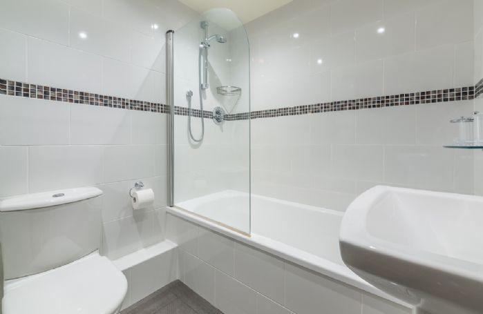 Ground floor: En-suite bathroom with bath and overhead shower