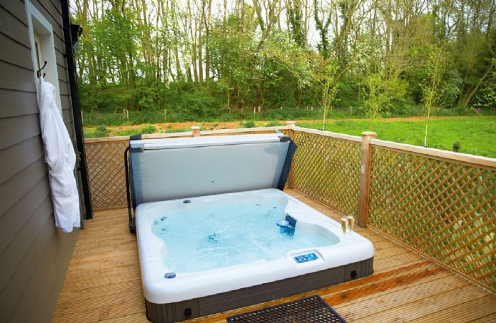 Decked area with garden furniture and hot tub
