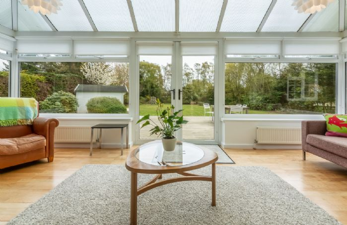 Ground floor: Sunroom conservatory with double doors that open on to a large sundeck