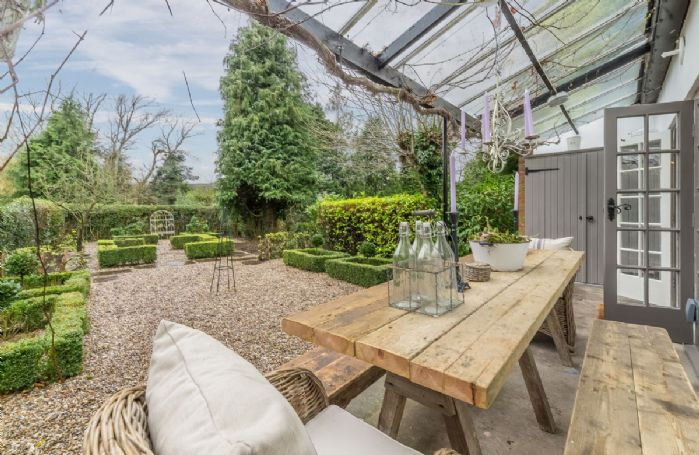 At the back of the property is a full length terrace, with glazed canopy over and dining table and chairs
