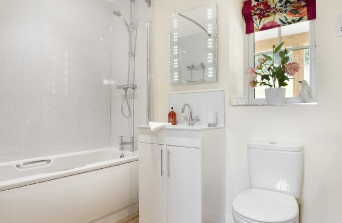 First floor: En-suite bathroom with bath and shower over