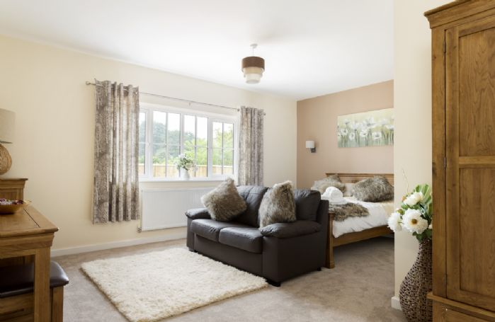 Ground floor: Double bedroom with 5' king-size bed, seating area with TV and en-suite bathroom