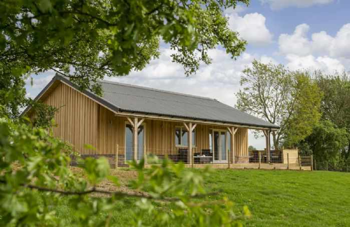 This larch clad, single storey property boasts a beautiful veranda commanding breath-taking views of rolling countryside
