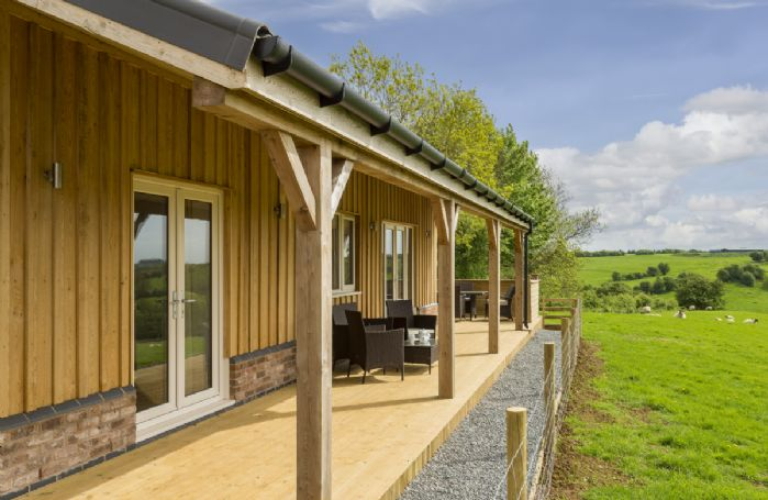 A wooden veranda with garden furniture looks on to open countryside