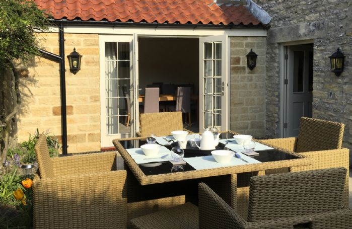 French doors from the dining room lead on to a paved patio with garden furniture