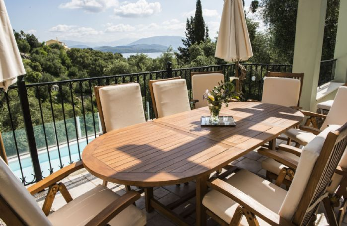 Terrace with teak dining furniture under a pergola, plus comfortable sofa and armchairs