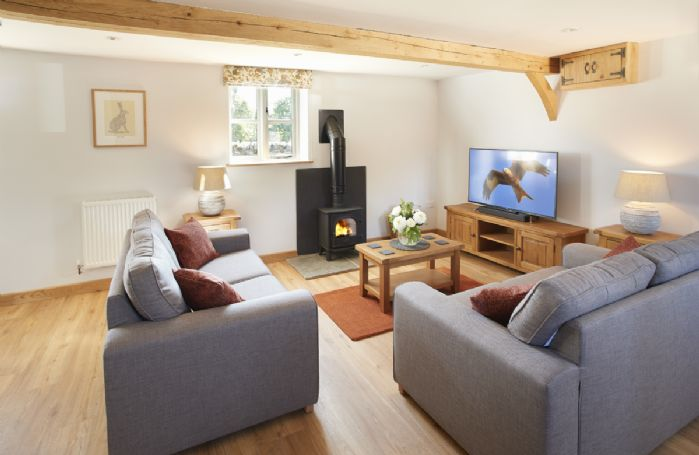 Ground floor:  Sitting room with wood burning stove and comfy sofas.