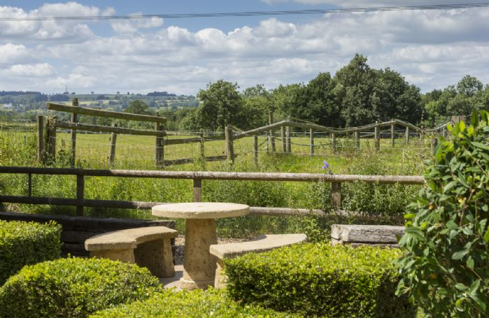 Enjoy the countryside views with this quiet seating area at the bottom on the garden.