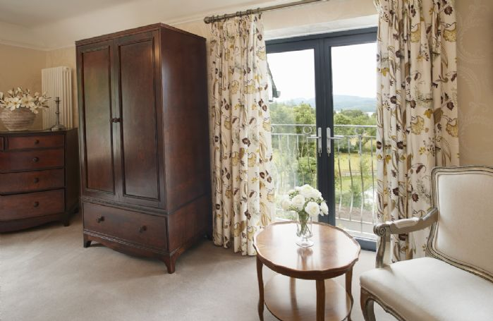 The master bedroom has dual aspect windows and Juliet balcony with lovely views across Lake Windermere