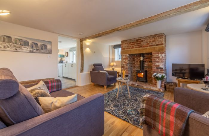Ground floor:  Sitting room with wooden floor and wood burning stove