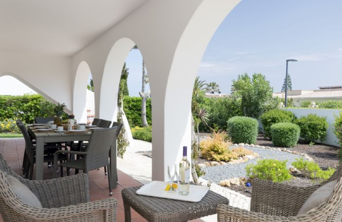 Covered terrace with outdoor furniture and views to the landscaped garden