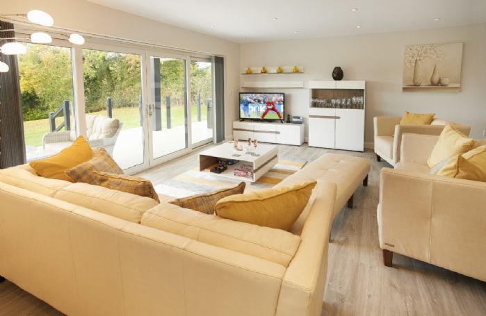 Ground floor: Spacious open plan sitting room with sliding doors to the wooden veranda