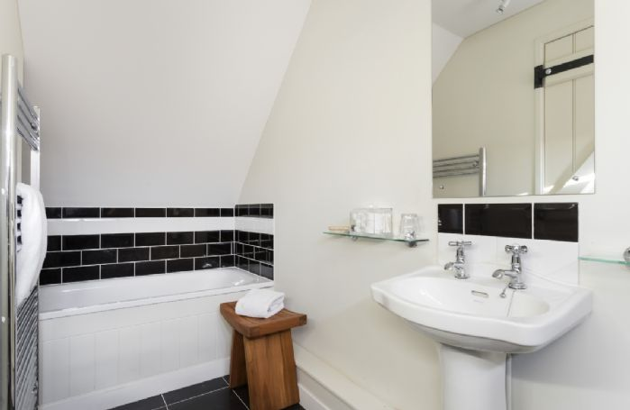 Above the entertainments room: En-suite with bath and handheld shower attachment