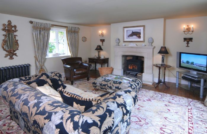 Ground floor: Sitting room, double aspect and flooded with natural light: there's ample comfy seating in front of the cosy wood burning stove