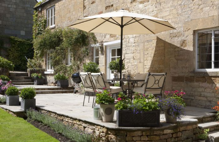 A beautiful garden with table and seating for eight, a barbecue and sun loungers