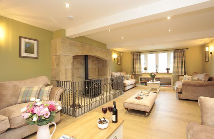 Ground floor: Sitting room with a large fireplace and comfortable sofas