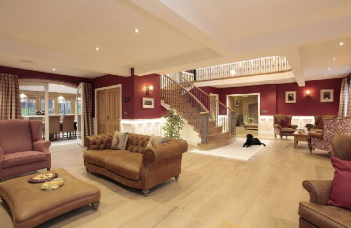 Ground floor: Chesterfield sofa, fireplace and double doors leading to the Orangery