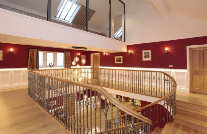 The elegant staircase leading up to the second floor and glass gallery landing