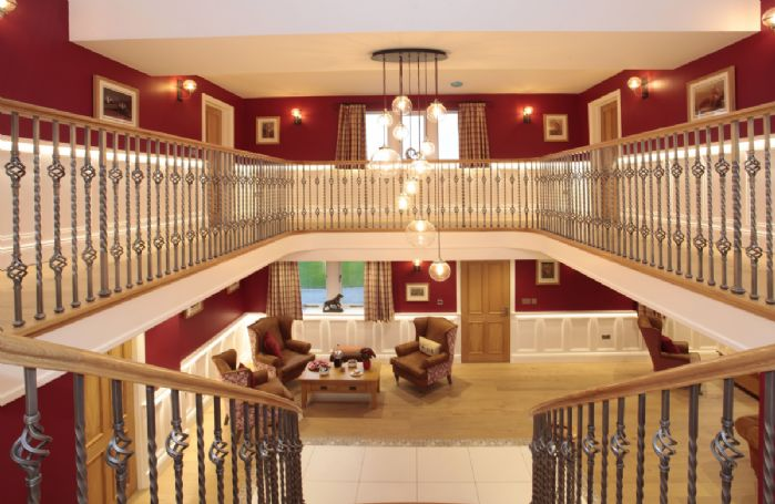 Grand hall with an elegant curved oak staircase leading up to the first floor