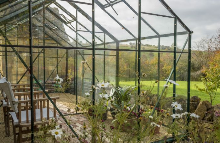 A greenhouse in the grounds offers a sheltered spot with glorious views