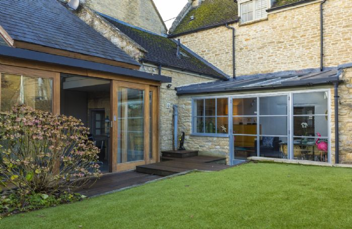 Sliding french doors lead onto the lawn and decking area
