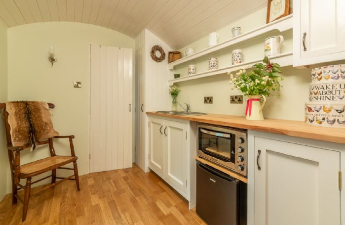 The kitchen, complete with fridge, electric combination oven and sink