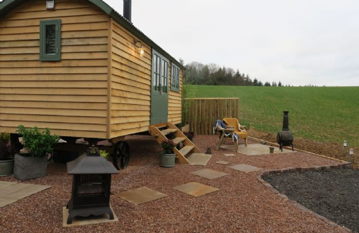 Side view of this delightful Shepherds hut with chimenea and solar lights
