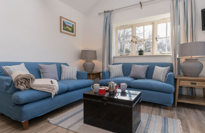Ground floor: Sitting room with comfortable sofas and lots of natural light