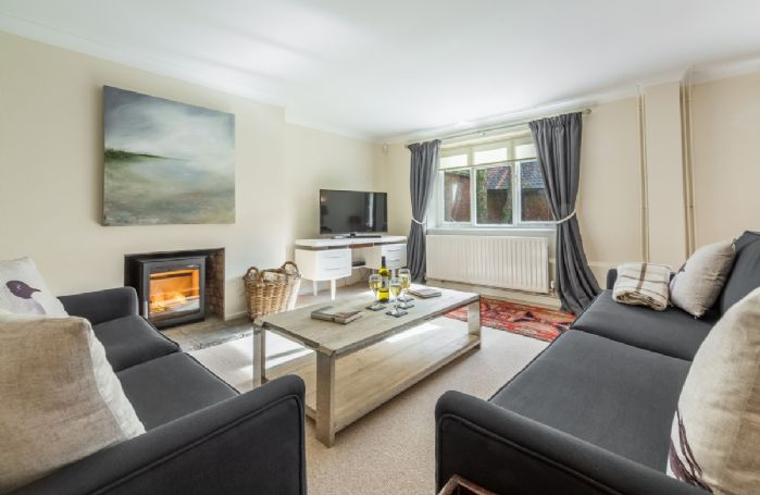 Ground floor: Elegant sitting room with ample seating and wood burner