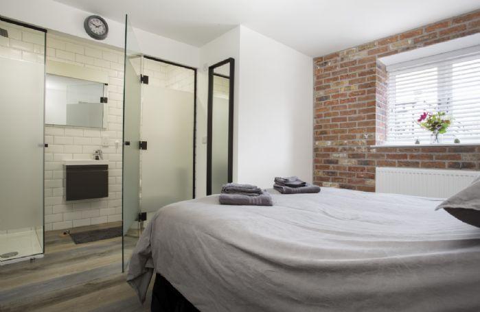 Ground floor: Bedroom two with en-suite shower room behind opaque glass doors