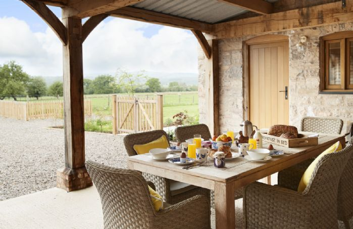 The garden room, a distinctive outdoor space with large dining table and rattan chairs to take in the lovely sunsets