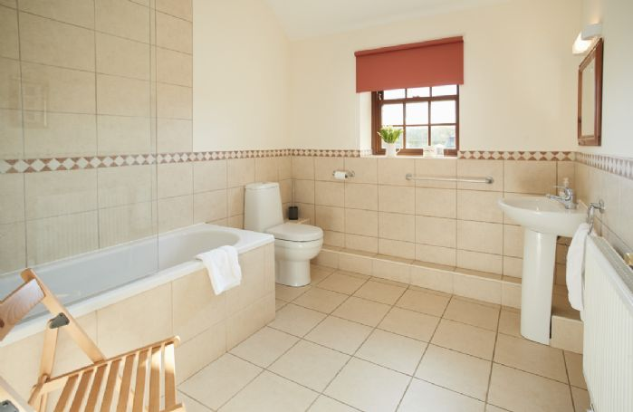 Ground floor: En-suite master bathroom with bath and shower over