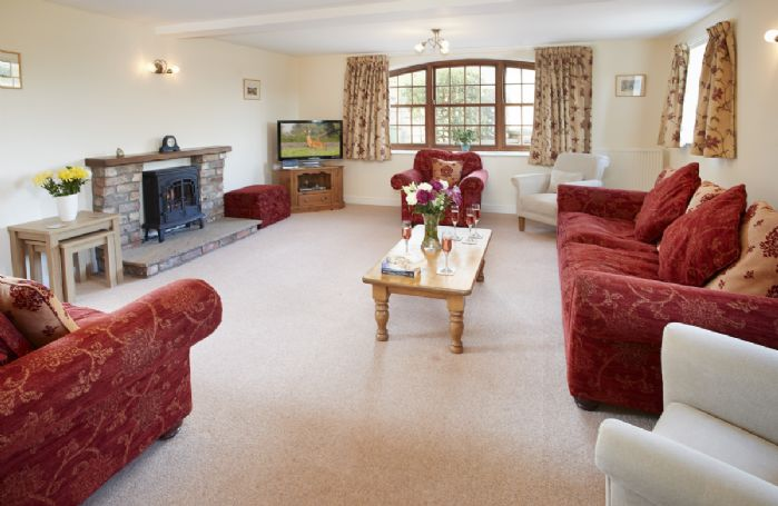 Ground floor: Spacious and comfortable sitting room with electric wood burner