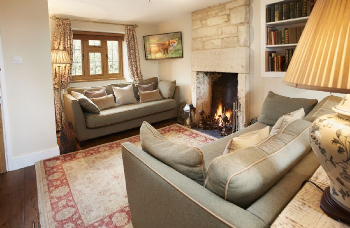 Ground floor: Sitting room with Cotswold stone fireplace and roaring open fire