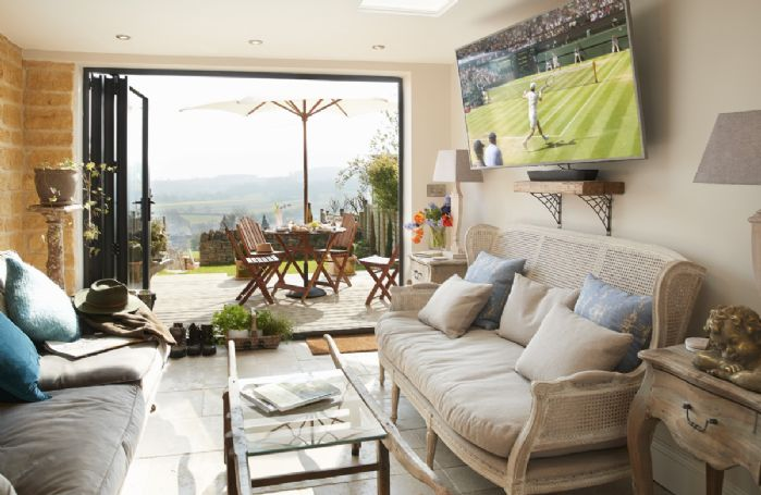 Lower ground floor:  The garden room with exposed stone wall, large Smart TV with Netflix and bi-fold doors to garden