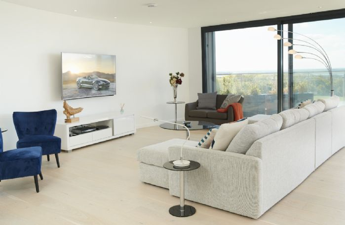 Second floor: Open plan sitting room with comfortable sofas and smart television