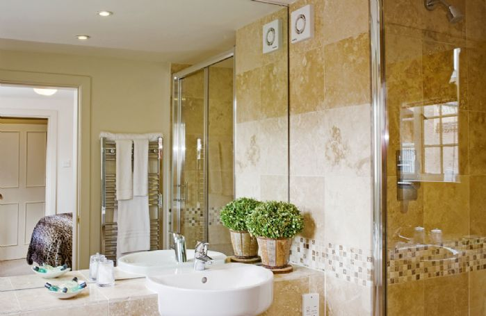 First floor: The bathroom has a large mirror and is fully tiled with heated towel rail