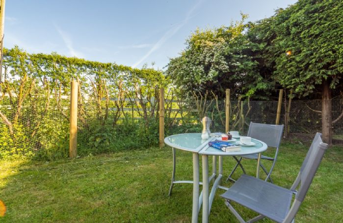 The garden area at Beau View Cottage with garden furniture and barbecue