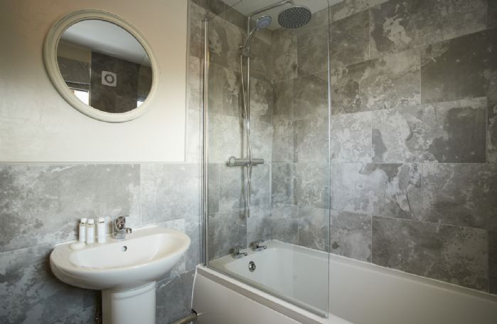 Ground floor: Modern bathroom with bath and shower over