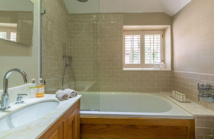 Ground floor: En-suite bathroom with shower over the bath