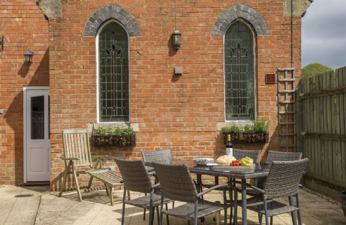 South facing garden area with garden furniture to the side of the property