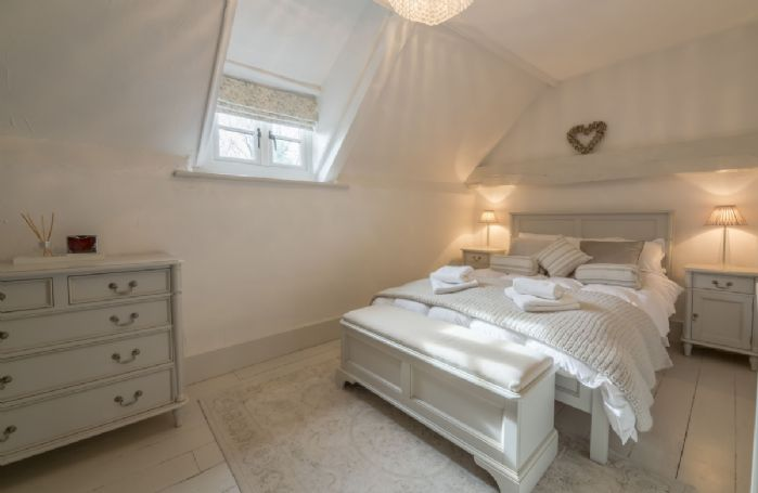 First floor: Main bedroom with 4'6 double bed with painted bedstead, feature brick chimney and painted floor boards
