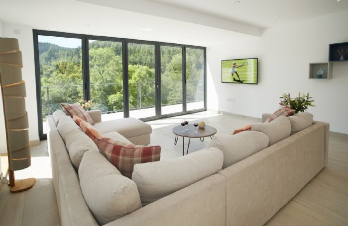 Ground floor: The spacious open plan sitting room with beautiful oak dining table seating eight guests