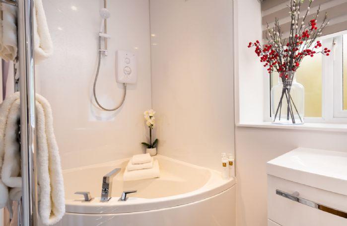 First floor: En-suite bathroom with corner bath