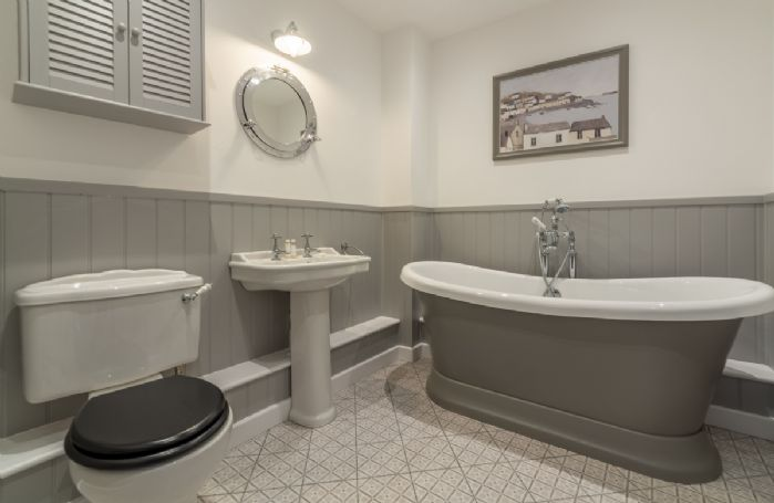 Ground floor: En-suite bathroom with freestanding roll-top bath and hand-held shower attachment