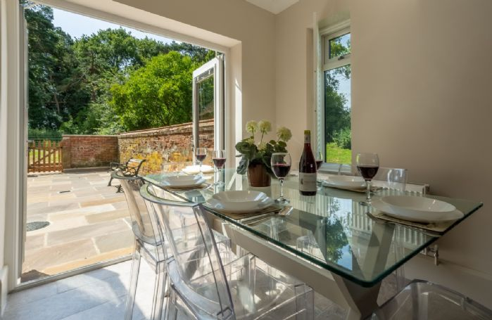Ground floor: Dining table seating six guests and french doors leading out to courtyard
