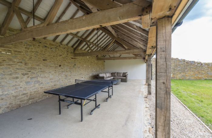 Covered area with table tennis and outdoor sofas, perfect for summer barbecues